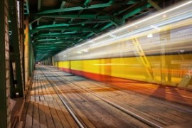Tram light trail in the lower part of the steel truss Gdanski Bridge in Warsaw, Poland, vanishing point perspective.